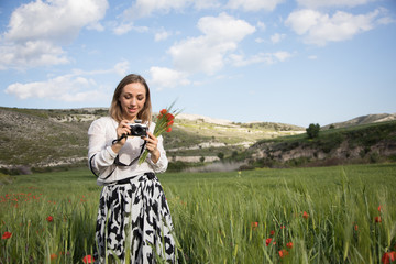 A young woman with camera in the blooming fields