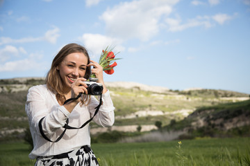 A young woman with camera in a good mood