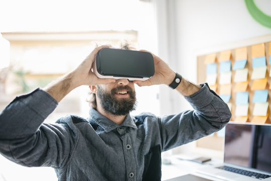 Man wearing Virtual Reality Glasses working on new project in his office