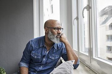 Mature man sitting at window, looking worried