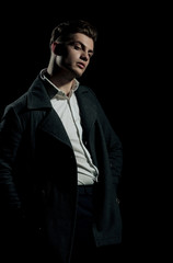 Handsome man posing in white shirt and dark coat