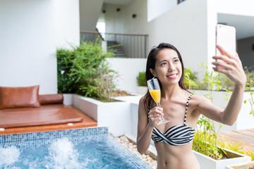 Woman taking selfie by mobile phone in jacuzzi pool