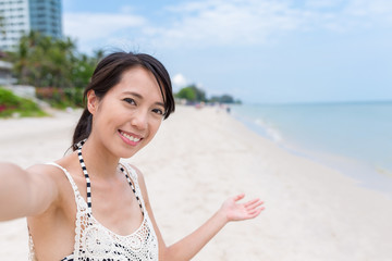 Woman holding camera to take selfie at beach