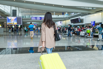 Rear view of woman walking with luggage in Hong Kong international airport