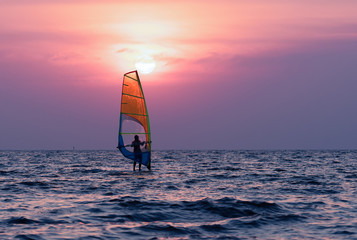 Man playing windsurfing at sunset.