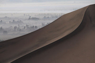 Dunes in the Peru desert and oasis wrapped in the fog in the distance South America