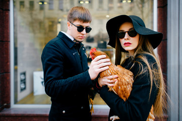 Portrait of beautiful couple of models in love in fashion clothes, black sunglasses, elegant hat standing in front of boutique showcase with chickens in hands and looking around. Unusual pets concept.