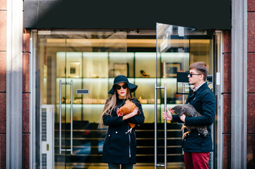 Man in black coat and opens door to a beautiful model long hair girl in glasses and elegant hat and fashion clothes coming out of boutique with chicken in hands after shopping. Celebrity pets concept.