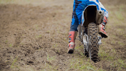 Motocross racer start riding his dirt Cross MX bike - rear view