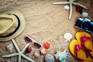 summer background frame,sandal beach,hat,sunglasses camera and starfish on sand