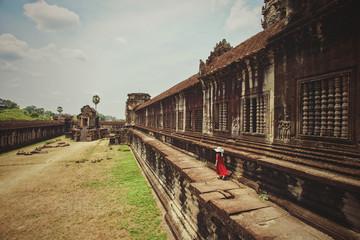 Girl in red dress walking through Angkor Wat temple, Siem Reap, Cambodia
