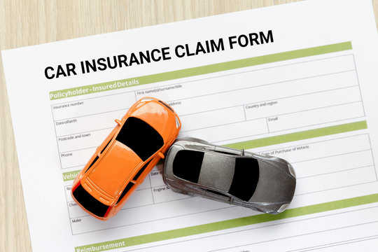 Top view of car insurance claim form with car toy crash on wooden desk.