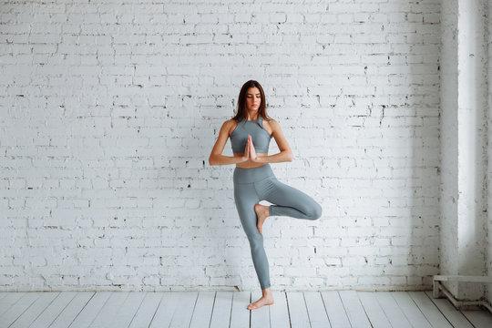 Young woman doing yoga, tree pose