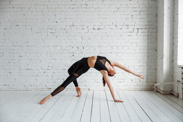 Portrait of beautiful young woman wearing black sportswear working out in studio. Fit sporty girl doing backbend exercise. Camatkarasana, Wild Thing or Flip-the-Dog posture. Full length. Side view