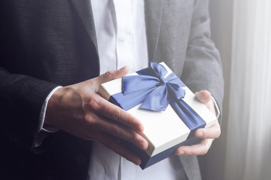 Man offering gift with blue ribbon