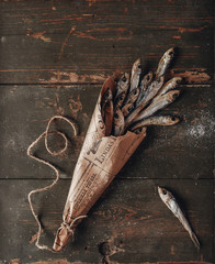 Dried salted small Baltic herring in a newspaper package on a green old shabby wooden background. View from above. Copy space