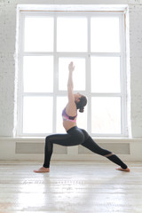 Young woman doing yoga indoors