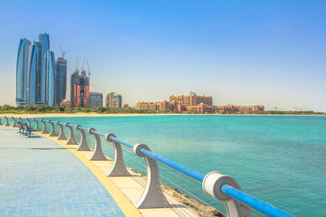 Dhabi skyline in the blue sky from Corniche in Abu Dhabi, United Arab Emirates, Middle East. Modern skyscrapers and landmark on background. Summer holidays concept. Sunny day, travel vacations.