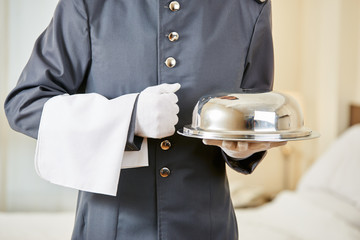 Hotel clerk serving food with cloche