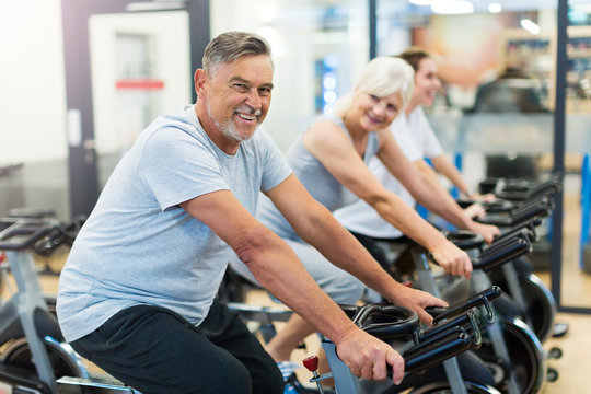 Confident seniors on exercise bikes in spinning class at gym