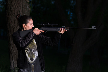 Girl with a gun in the woods.