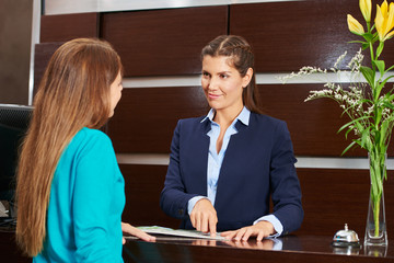Woman at hotel reception offering advice