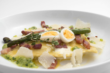 quail eggs and asparagus pasta on a white plate