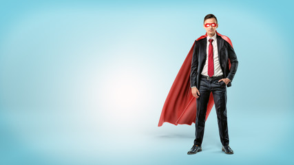 A self-assured businessman in a red cape and a mask standing with a hand in his pocket on blue background.