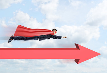 A businessman in a superhero cape flying straight through the clouds with a red arrow below him pointing forward.