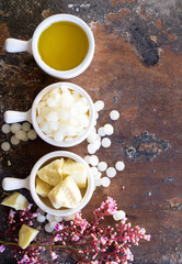 white cosmetic beeswax pellets, cocoa butter, natural oil in pot prepare for D.I.Y. projects, homemade natural lip balm.