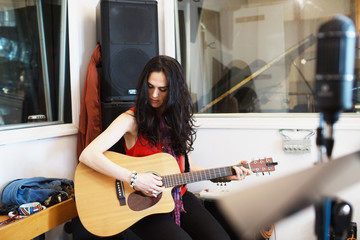 Young woman playing acoustic guitar at a recording studio