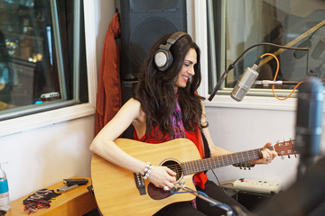 Smiling young woman playing acoustic guitar in recording studio