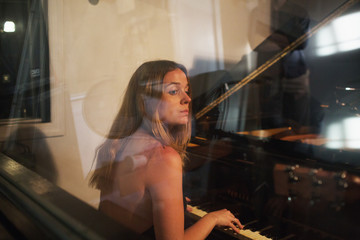 Young woman playing piano at a recording studio