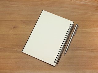 Notebook with white pages and pen on wooden table.