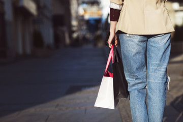 Midsection of woman with shopping bags standing on city street