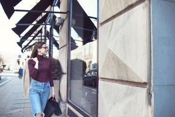 Woman looking in shop window while walking on sidewalk