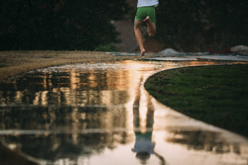 Low section of boy running on wet footpath in park during sunset