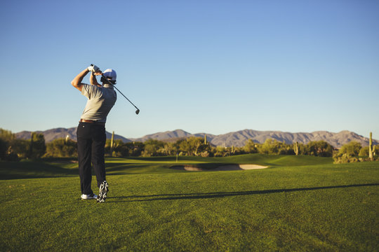 Rear view of man playing golf against clear blue sky
