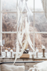 Decoration in boho style. White feathers, candles