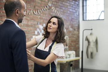 Female fashion designer talking to businessman while taking measurement at workshop