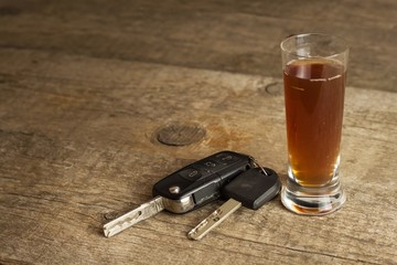 Alcohol and driving. Danger on the roads. Alcoholic behind the wheel. Car keys on the bar.