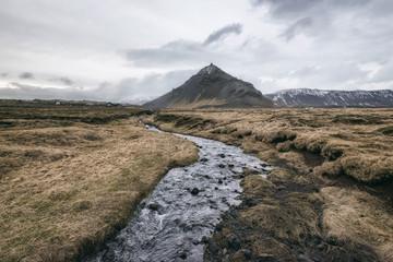 Stream amidst field against sky