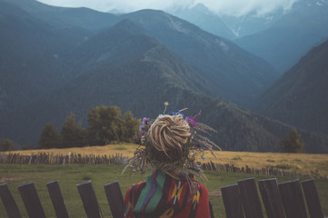 Rear view of woman with dread locks hair bun standing on field against mountains