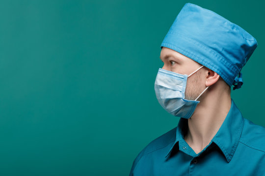 profile portrait of male surgeon in mask on blue background, close up. copy space