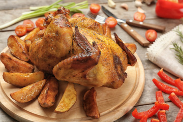 Board with roasted beer can chicken on wooden table, closeup