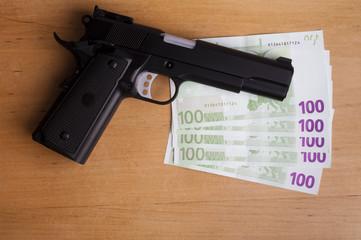 Un révolver posé sur des billets de banque
