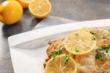 Plate with tasty chicken piccata on table