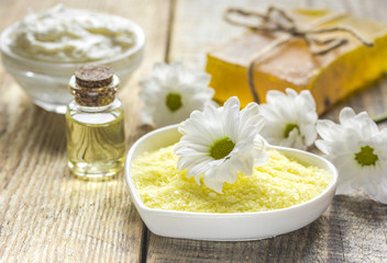 organic cosmetics with camomile extract on wooden table background
