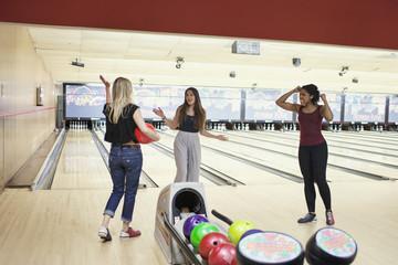 Three young women bowling.