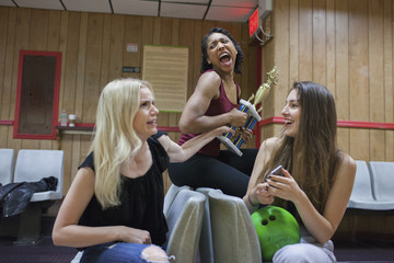 Three young women with a trophy in a bowling alley.